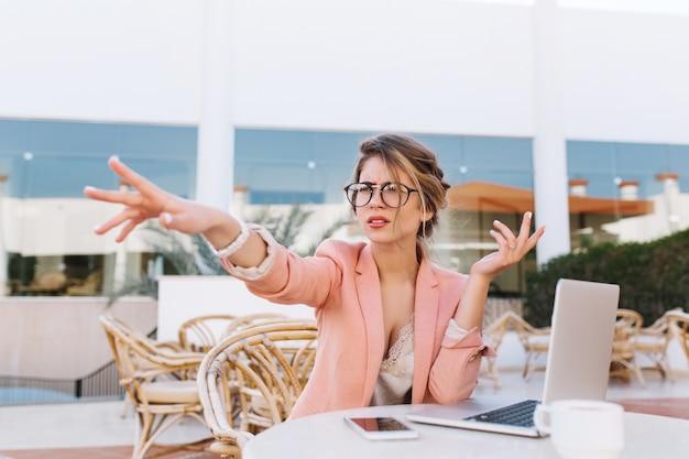 テーブルの上のラップトップで屋外カフェに座っている若いビジネス女性、手方向を指している深刻な女性は、不信感で何かを見た。スタイリッシュなピンクのジャケット、メガネ、白い時計を着ています。