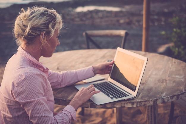 야외에 앉아서 노트북으로 작업하는 젊은 비즈니스 우먼-대체 사무실 및 라이프 스타일을위한 무선 무료 인터넷 연결-프리랜서 디지털 노매드 어디서나 워크 스테이션