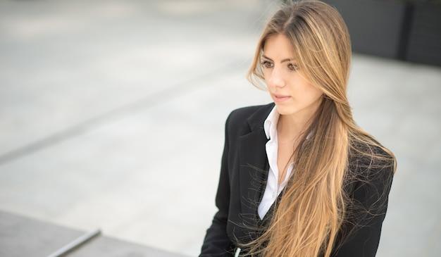 ベンチに屋外に座っている若いビジネス女性