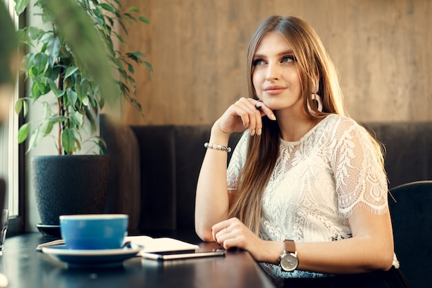 Young business woman sitting at the table in a coffee shop and making notes