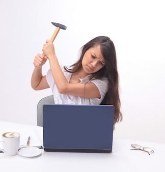 机の後ろに座ってラップトップを壊す若いビジネス女性