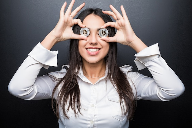 Young business woman smile cover eyes with bitcoin isolated on black wall