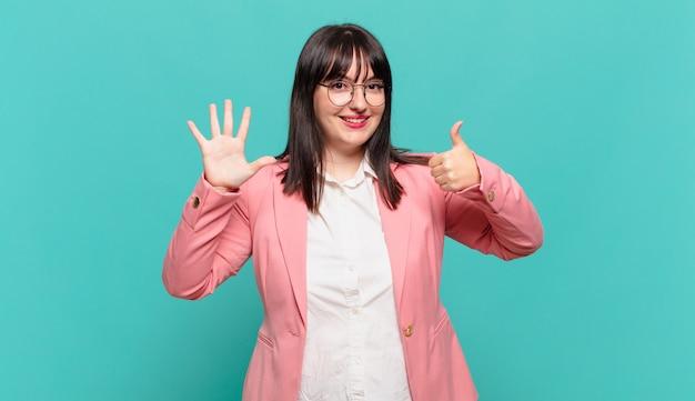 Молодая деловая женщина улыбается и выглядит дружелюбно, показывает номер шесть или шестой рукой вперед, отсчитывая