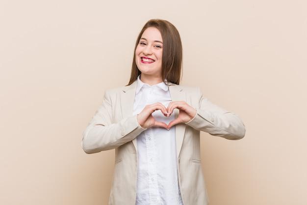 笑顔と手でハートの形を示す若いビジネス女性。