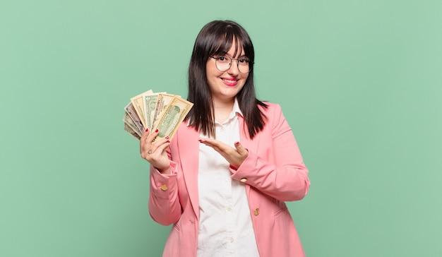 쾌활하게 웃고 행복하고 손바닥으로 복사 공간에서 개념을 보여주는 젊은 비즈니스 여성