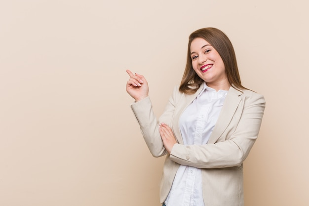 Young business woman smiling cheerfully pointing with forefinger away.