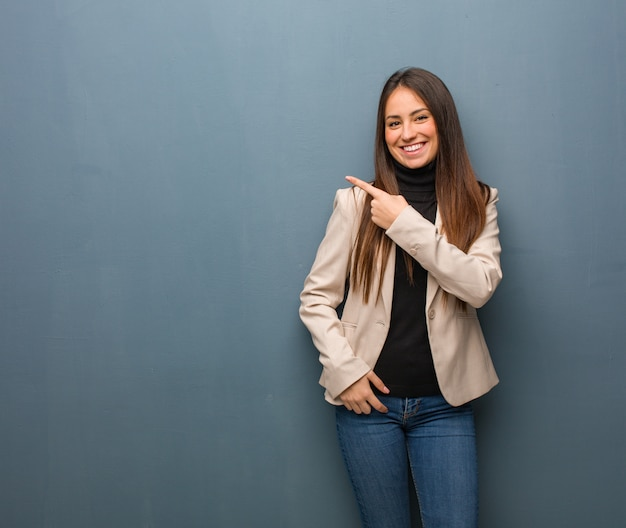 Young business woman smiling and pointing to the side