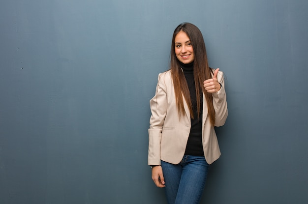 Young business woman smiling and raising thumb up