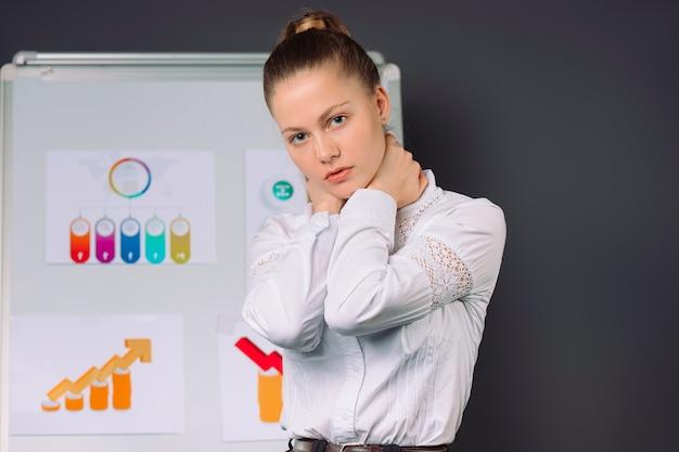 若いビジネスウーマンは、ビジネスとパンデミックグレーの会議の疲労の間に彼女の首を絞る
