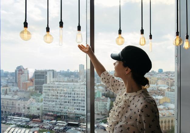 Молодая деловая женщина, стоящая у окна, наслаждаясь панорамой города с потрясающим панорамным видом и лампочками