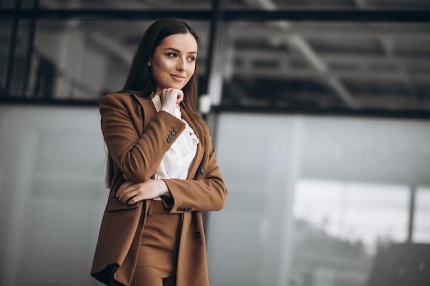 Молодая бизнес-леди стоя в костюме в офисе