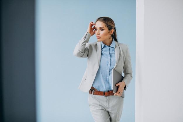 Молодая бизнес-леди стоя в изолированном офисе
