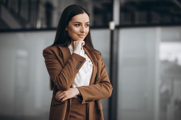 Giovane donna d'affari in piedi in tuta in ufficio