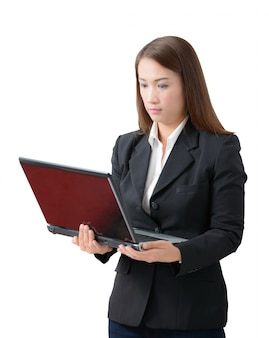 Young business woman, standing wearing a white shirt and black suit holding a laptop pc.