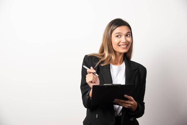 白い壁にクリップボードを持って立っている若いビジネス女性。