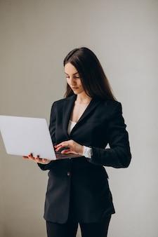 オフィスでラップトップを持って立っている若いビジネス女性