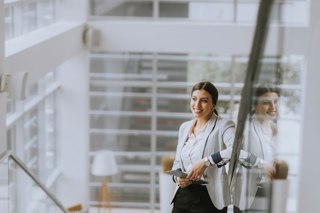 Young business woman stands on the stairs at the office and use mobile phone