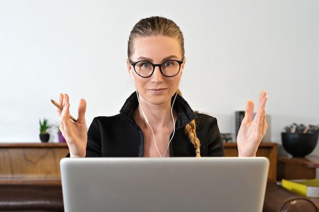 Молодой бизнес-леди студент-учитель звонит на портативный компьютер, разговаривает по веб-камере