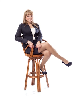 Young business woman in a suit, sitting on  bar stool.