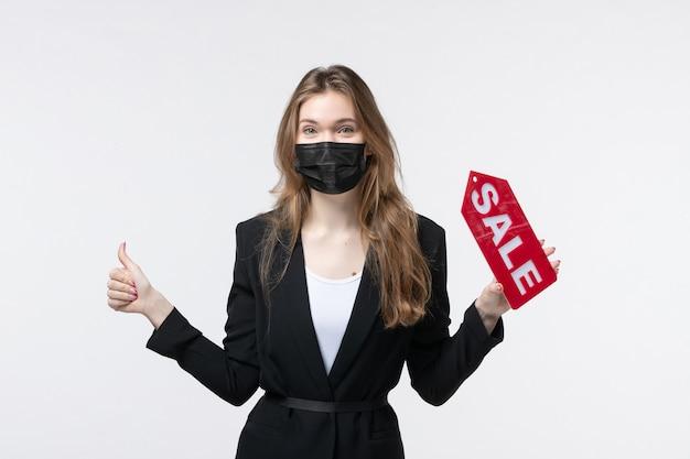 Giovane donna d'affari in tuta che indossa la sua maschera medica e mostra la vendita facendo un gesto ok sul muro bianco isolato