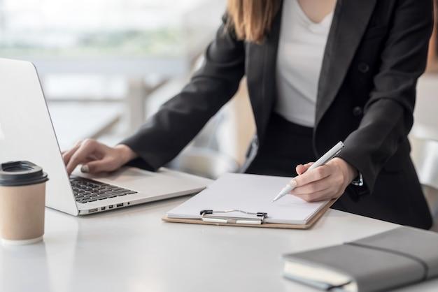 Молодая деловая женщина делает заметки и с помощью ноутбука в офисе.