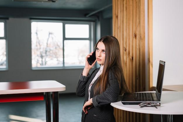 Молодой бизнес женщина разговаривает по телефону за столом