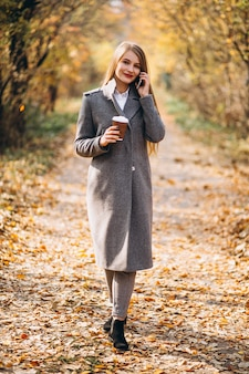 Young business woman talking on the phone and drinking coffee