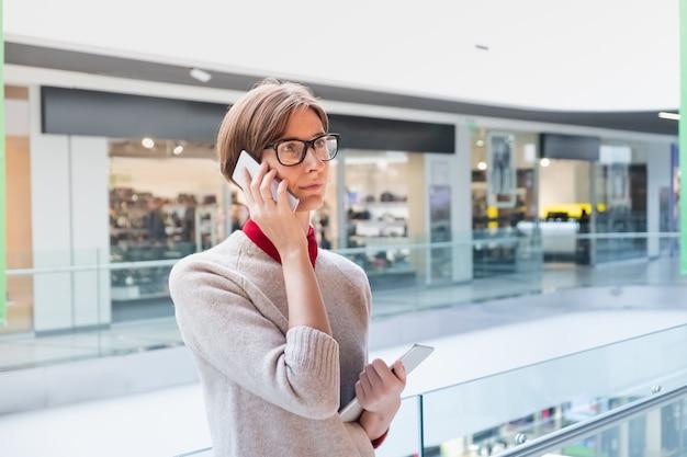 ショッピングモールで電話で話している若いビジネス女性。タブレットを持っているデパートでスマートカジュアルな服装の女性人