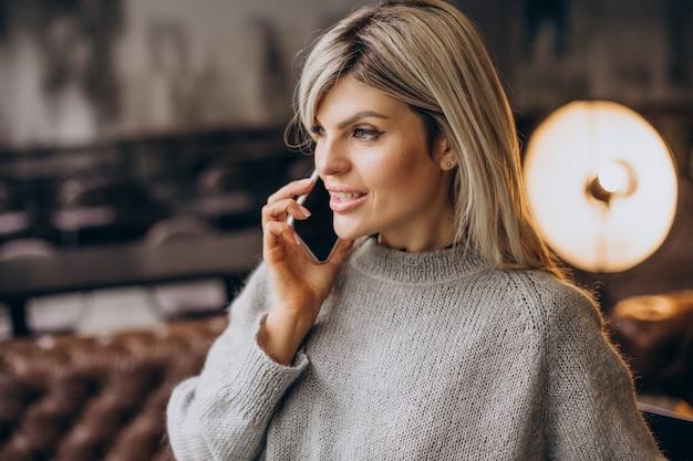 Молодая деловая женщина разговаривает по телефону в кафе