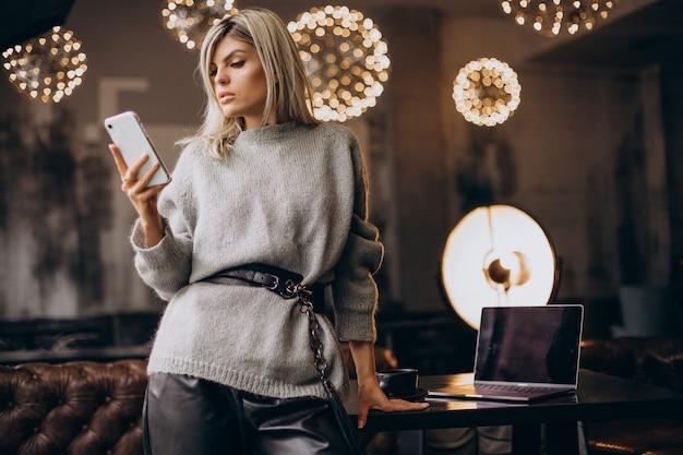 Giovane donna d'affari che parla al telefono in un caffè