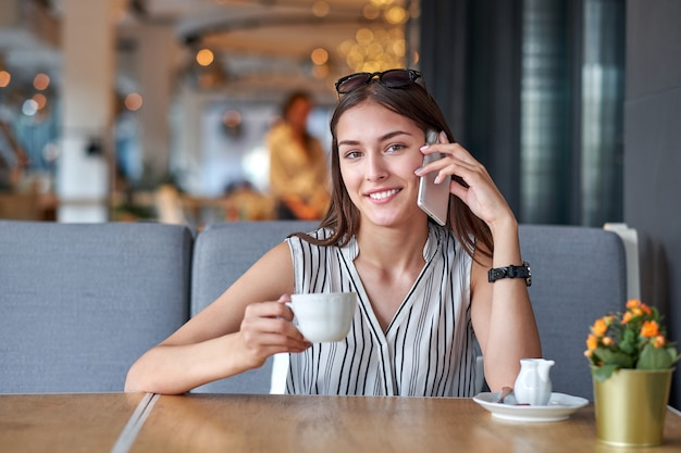 Young business woman talking on the phone in coffee shop