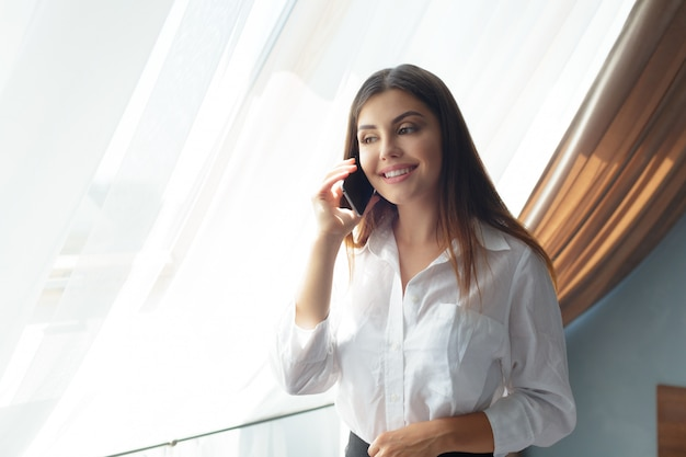 Young business woman talking with phone in the hotel.