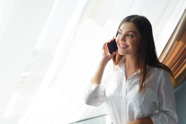 Молодой бизнес женщина разговаривает с телефоном в отеле.