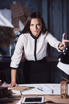 Documenti di lancio della giovane donna di affari alla macchina fotografica. deluso e infastidito dal progetto fallito.