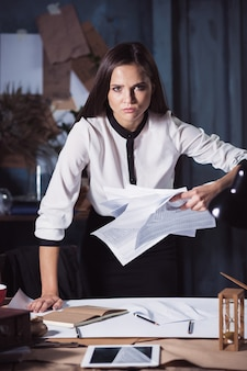 Young business woman throwing documents. disappointed and annoyed by unsuccessful project.
