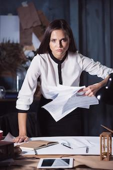 Giovane donna di affari che getta i documenti. deluso e infastidito dal progetto infruttuoso.
