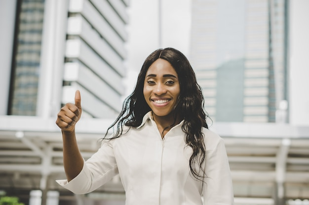 Young business woman thumbs up
