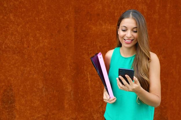 防錆背景とコピースペースを持つスマートフォンで入力する若いビジネス女性。