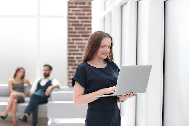 젊은 비즈니스 여성은 복사 공간이 있는 사무실 .photo에 서 있는 동안 노트북을 사용합니다.