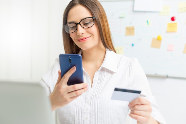 Young business woman uses a mobile phone and a credit card for online payment.