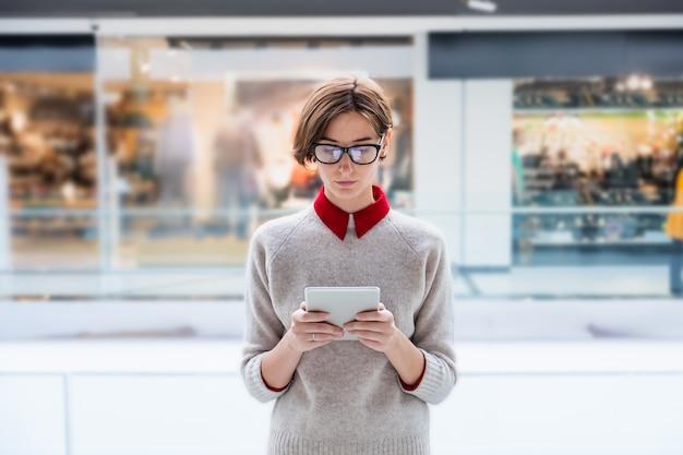 Молодая бизнес-леди с помощью планшета в торговом центре. женщина в элегантной повседневной одежде в универмаге, работающем с технологиями