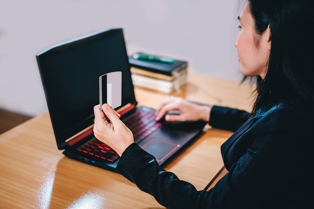Young business woman using credit card and working on computer notebook