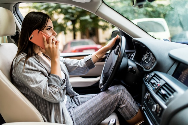 Young business woman utilizzando il suo telefono mentre si guida l'auto