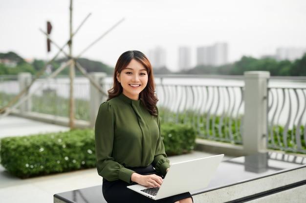 Молодая бизнес-леди, используя ноутбук, сидя в парке.