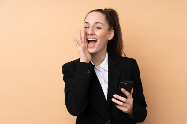 Молодая бизнес-леди используя мобильный телефон над изолированной стеной крича с широко открытым ртом