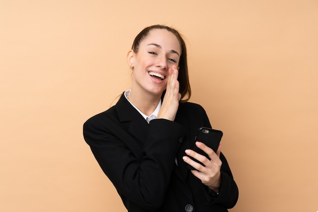 何かをささやく分離壁を越えて携帯電話を使用して若いビジネス女性
