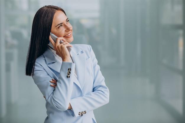 Молодая деловая женщина с помощью мобильного телефона