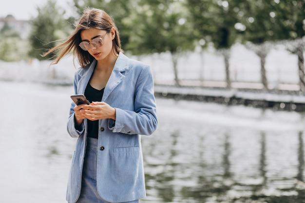 公園で携帯電話を使用して若いビジネス女性
