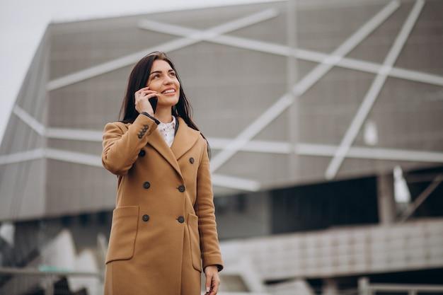 電話を使用して若いビジネス女性