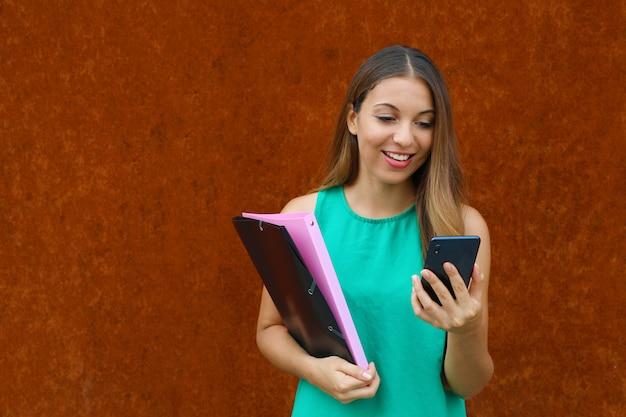 コピースペースで錆の背景にスマートフォンを使用して若いビジネス女性。